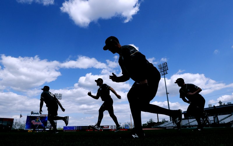 In this Monday, May 13, 2019 photo, Quad Cities River Bandits players warm up before a Class-A Midwest League baseball game against the Cedar Rapids Kernels in Cedar Rapids, Iowa. (AP Photo/Charlie Neibergall)
