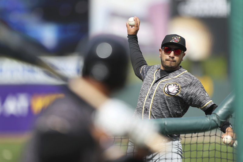 In this Monday, May 13, 2019 photo, Quad Cities River Bandits manager Ray Hernandez, right, throws during batting practice before a Class-A Midwest League baseball game against the Cedar Rapids Kernels in Cedar Rapids, Iowa. (AP Photo/Charlie Neibergall)