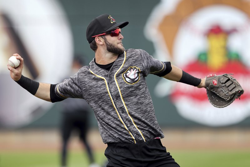 In this Monday, May 13, 2019 photo, Quad Cities River Bandits infielder David Hensley warms up before a Class-A Midwest League baseball game against the Cedar Rapids Kernels in Cedar Rapids, Iowa. (AP Photo/Charlie Neibergall)