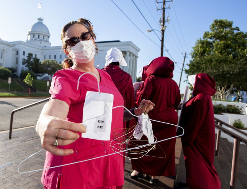Laura Stiller hands out coat hangers as she talks about illegal abortions during a rally against a ban on nearly all abortions outside of the Alabama State House in Montgomery, Ala. (Mickey Welsh/The Montgomery Advertiser via AP)