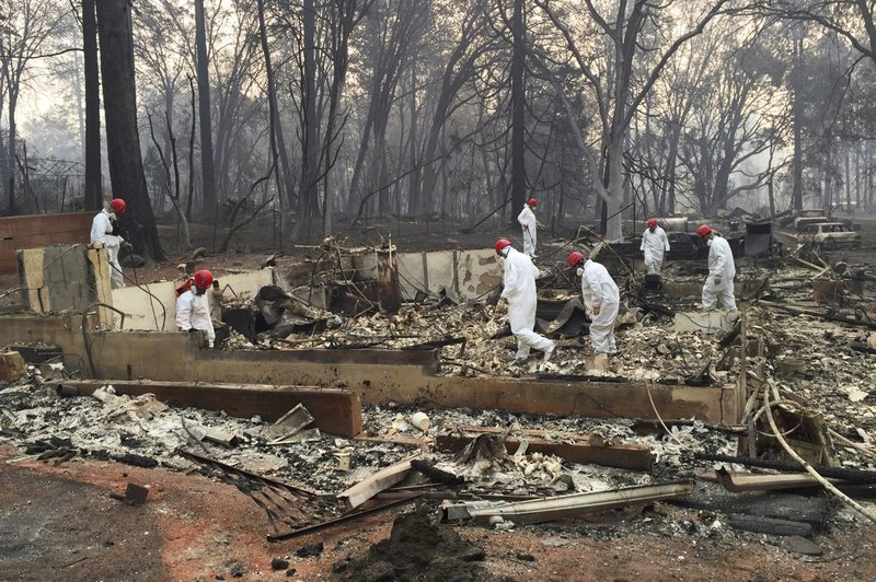 FILE - In this Nov. 15, 2018 file photo, volunteer rescue workers search for human remains in the rubble of homes burned in the Camp Fire in Paradise, Calif. (AP Photo/Terry Chea, File)
