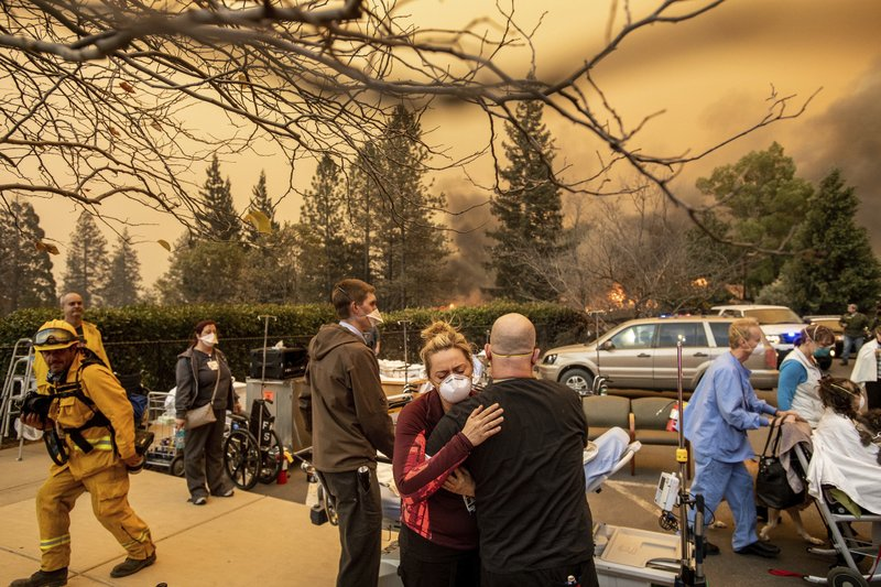 FILE - This Nov. 8, 2018, file photo shows Nurse Cassie Lerossignol hugs as coworker as the Feather River Hospital burns while the Camp Fire rages through Paradise, Calif. (AP Photo/Noah Berger, File)