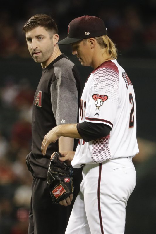 Arizona Diamondbacks starting pitcher Zack Greinke leaves the field with a trainer during the eighth inning of a baseball game against the Pittsburgh Pirates in Phoenix, Wednesday, May 15, 2019. (AP Photo/Matt York)