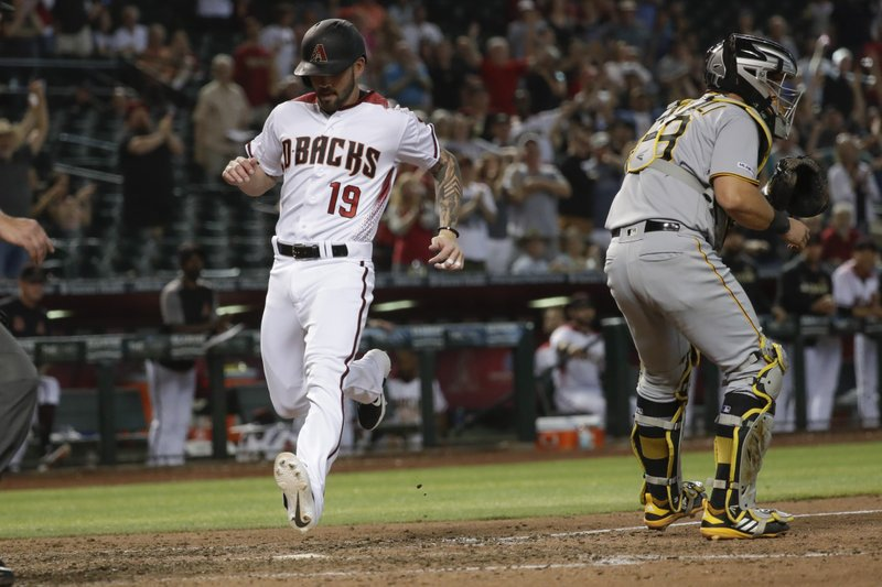 Arizona Diamondbacks' Blake Swihart, left, scores past Pittsburgh Pirates catcher Francisco Cervelli on inside the park home run during the eighth inning of a baseball game in Phoenix, Wednesday, May 15, 2019. (AP Photo/Matt York)