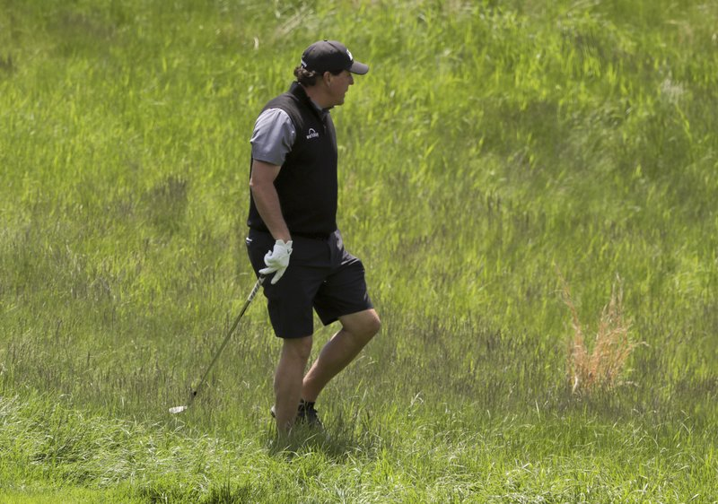 Phil Mickelson looks for his ball in the rough on the 10th hole during a practice round for the PGA Championship golf tournament, Wednesday, May 15, 2019, at Bethpage Black in Farmingdale, N. (AP Photo/Charles Krupa)