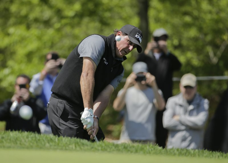 Phil Mickelson chips a shot onto the 13th green during a practice round for the PGA Championship golf tournament, Wednesday, May 15, 2019, at Bethpage Black in Farmingdale, N. (AP Photo/Seth Wenig)