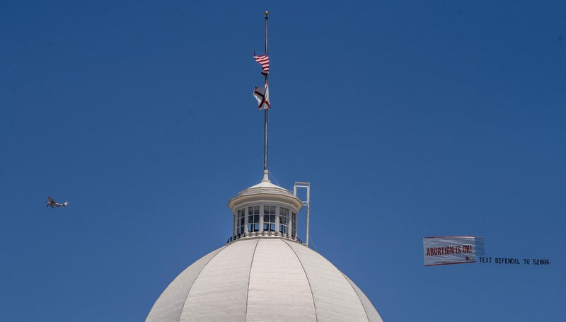 Legal abortion supporters fly a banner reading Abortion is OK over the Alabama State Capitol building in downtown Montgomery, Ala. (Mickey Welsh/The Montgomery Advertiser via AP)