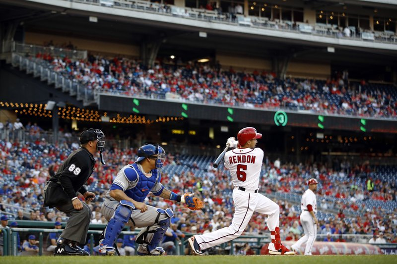 Washington Nationals' Anthony Rendon, right, hits a ground rule double in front of New York Mets catcher Wilson Ramos and home plate umpire Cory Blaser in the first inning of a baseball game, Wednesday, May 15, 2019, in Washington. (AP Photo/Patrick Semansky)