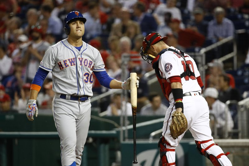 New York Mets' Michael Conforto, left, walks off the field past Washington Nationals catcher Yan Gomes after striking out swinging in the fourth inning of a baseball game, Wednesday, May 15, 2019, in Washington. (AP Photo/Patrick Semansky)