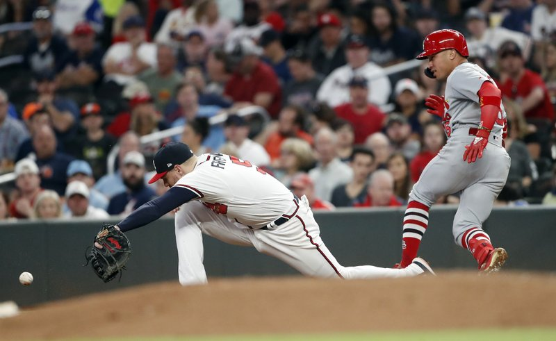 St. Louis Cardinals' Kolten Wong (16) is safe at first base with a single as the ball gets past Atlanta Braves first baseman Freddie Freeman (5) in the seventh inning of a baseball game Wednesday, May 15, 2019, in Atlanta. (AP Photo/John Bazemore)