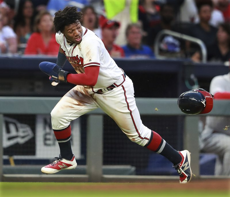 Atlanta Braves Ronald Acuna Jr. steals third base and loses his helmet going home to score on the errant throw during the third inning of a baseball game against the St. (Curtis Compton/Atlanta Journal-Constitution via AP)