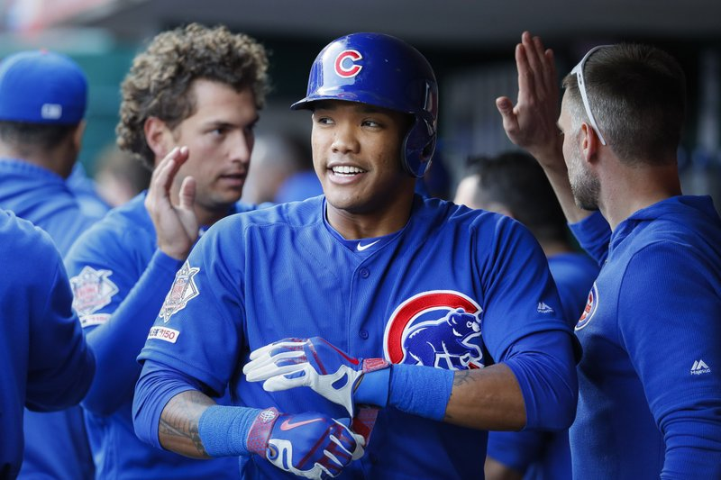 Chicago Cubs' Addison Russell celebrates in the dugout after hitting a two-run home run off Cincinnati Reds starting pitcher Sonny Gray during the second inning of a baseball game Wednesday, May 15, 2019, in Cincinnati. (AP Photo/John Minchillo)