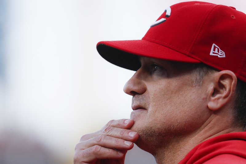 Cincinnati Reds manager David Bell works in the dugout during the fourth inning of a baseball game against the Chicago Cubs, Wednesday, May 15, 2019, in Cincinnati. (AP Photo/John Minchillo)