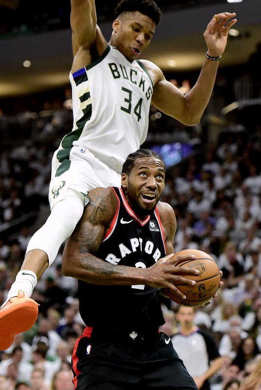 Toronto Raptors forward Kawhi Leonard (2) is fouled by Milwaukee Bucks forward Giannis Antetokounmpo (34) during the second half in Game 1 of the NBA basketball playoffs Eastern Conference final in Milwaukee on Wednesday, May 15, 2019. (Frank Gunn/The Canadian Press via AP)