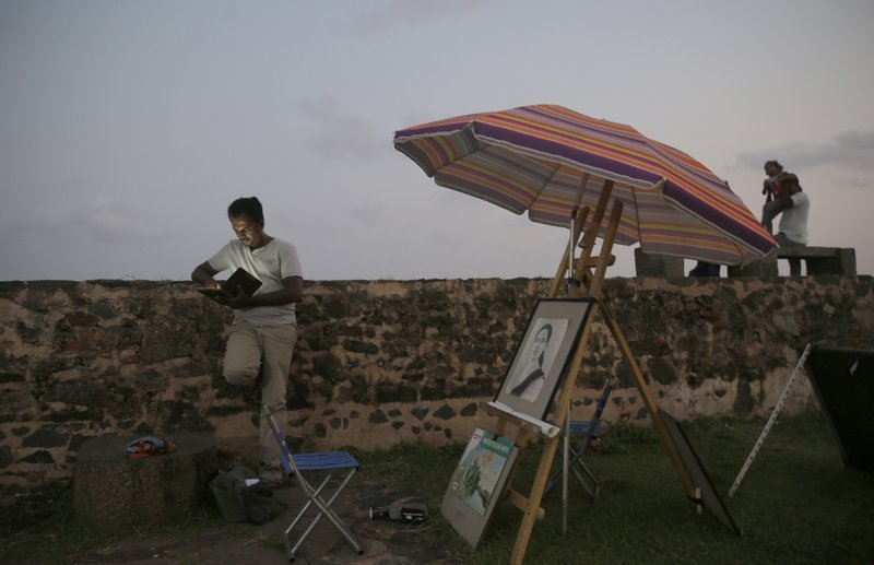 In this Friday, May 10, 2019, photo, a Sri Lankan street painter looks at his mobile phone as locals stand along the 17th century Dutch built rampart of the Galle fort in Galle, Sri Lanka. (AP Photo/Eranga Jayawardena)