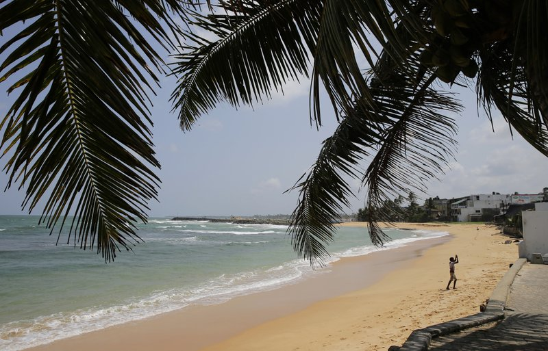 In this Friday, May 10, 2019, photo, a boy walks on a beach in Hikkaduwa, Sri Lanka. Sri Lanka was the Lonely Planet guide's top travel destination for 2019, but since the Easter Sunday attacks on churches and luxury hotels, foreign tourists have fled. (AP Photo/Eranga Jayawardena)