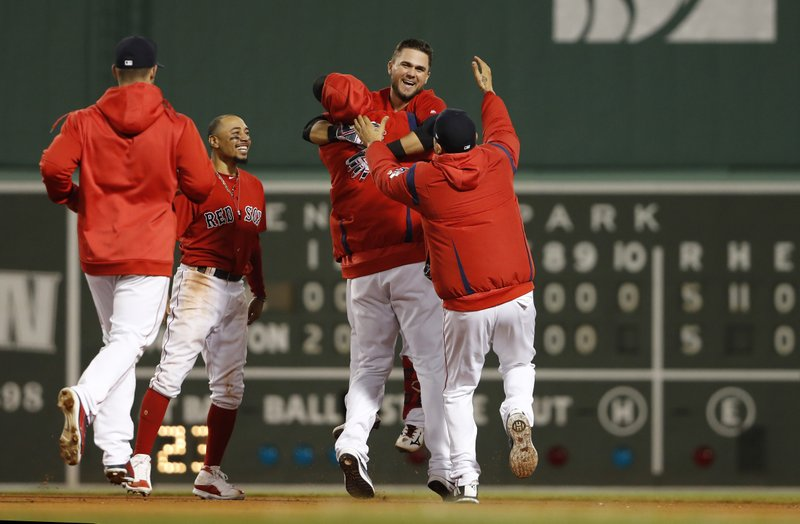 Boston Red Sox's Michael Chavis, second from right, is mobbed by teammates after his game-ending RBI single during the 10th inning of a baseball game against the Colorado Rockies on Wednesday, May 15, 2019, at Fenway Park in Boston. (AP Photo/Winslow Townson)