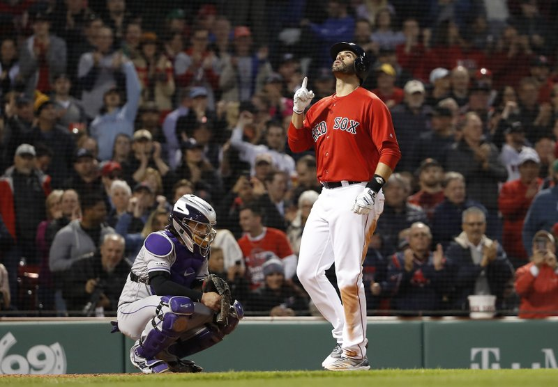 Boston Red Sox's J.D. Martinez points skyward as he crosses home plate in front of Colorado Rockies catcher Tony Wolters after his two-run home run during the third inning of a baseball game Wednesday, May 15, 2019, at Fenway Park in Boston. (AP Photo/Winslow Townson)
