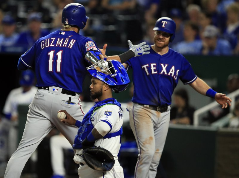 Texas Rangers' Ronald Guzman (11) celebrates his two-run home run with teammate Logan Forsythe, right, during the sixth inning of a baseball game against the Kansas City Royals at Kauffman Stadium in Kansas City, Mo. (AP Photo/Orlin Wagner)