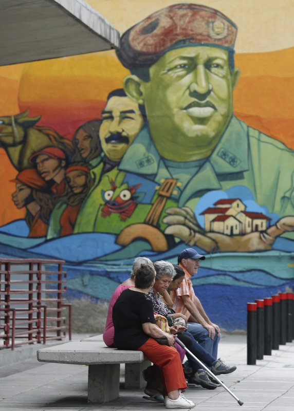 Residents rest on a bench backdropped by a mural featuring Venezuela's late President Hugo Chavez and President Nicolas Maduro, in Caracas, Venezuela, Friday, May 3, 2019. (AP Photo/Martin Mejia)