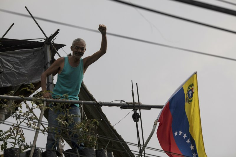 A man holds up his fist to show support for the government of President Nicolas Maduro, from his balcony which overlooks a public square where residents socialize and dance in Caracas, Venezuela, at sunset Saturday, May 11, 2019. (AP Photo/Rodrigo Abd)