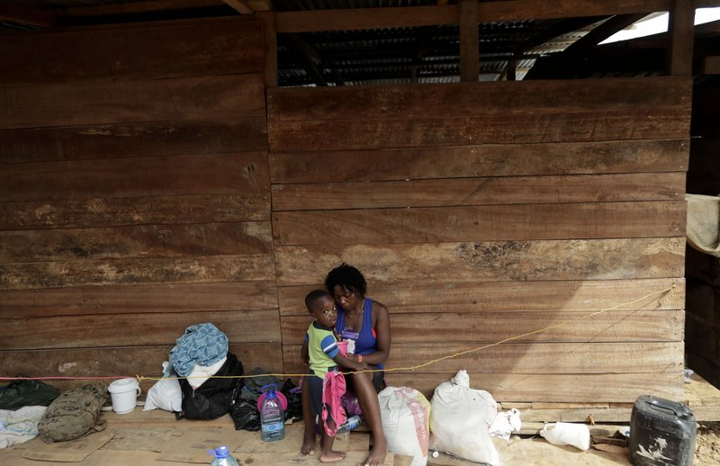 In this May 10, 2019 photo, a migrant woman and her son rest under a wooden house in Peñitas, Darien Province, Panama. (AP Photo/Arnulfo Franco)