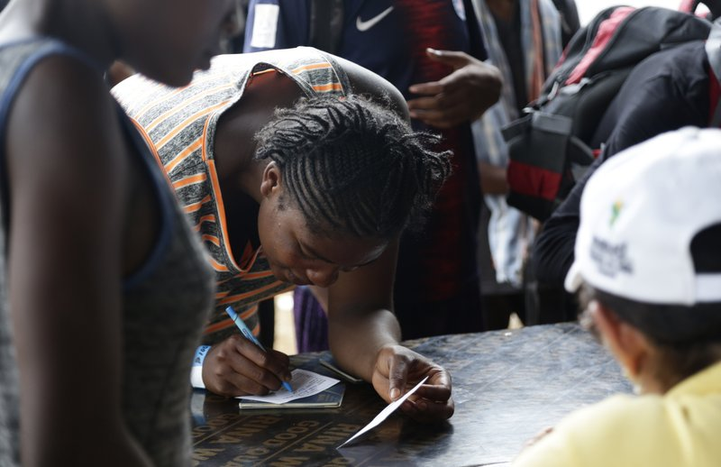 In this May 10, 2019 photo, a migrant signs a document after being vaccinated in Peñitas, Darien Province, Panama. (AP Photo/Arnulfo Franco)