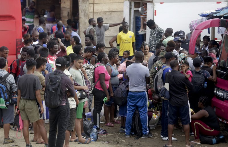 In this May 10, 2019 photo, a group migrants wait for a bus to take them north, in Peñitas, Darien Province, Panama. (AP Photo/Arnulfo Franco)