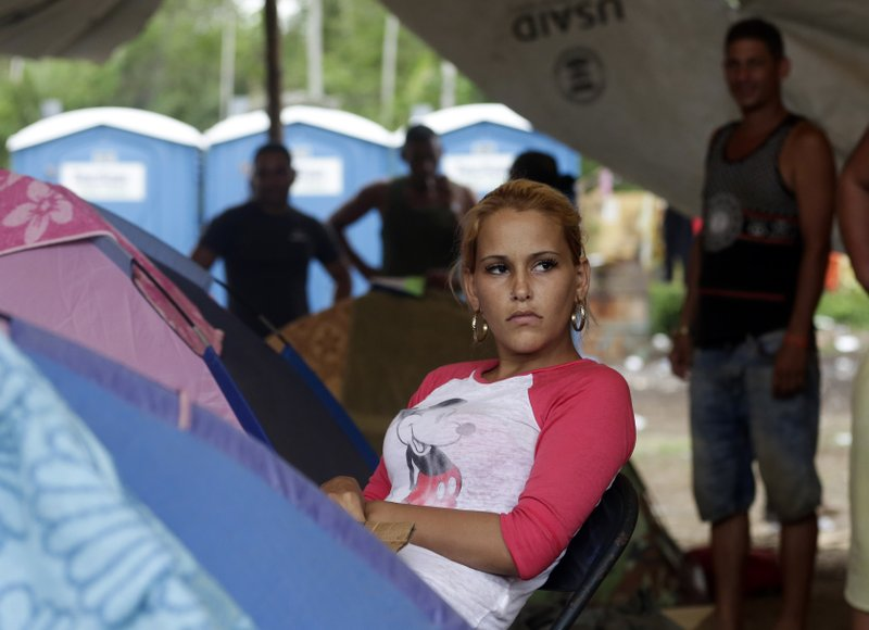 In this May 10, 2019 photo, Cuban migrant Lisandra Perez Molina, rests next to her tent at a shelter in Peñitas, Darien Province, Panama. (AP Photo/Arnulfo Franco)