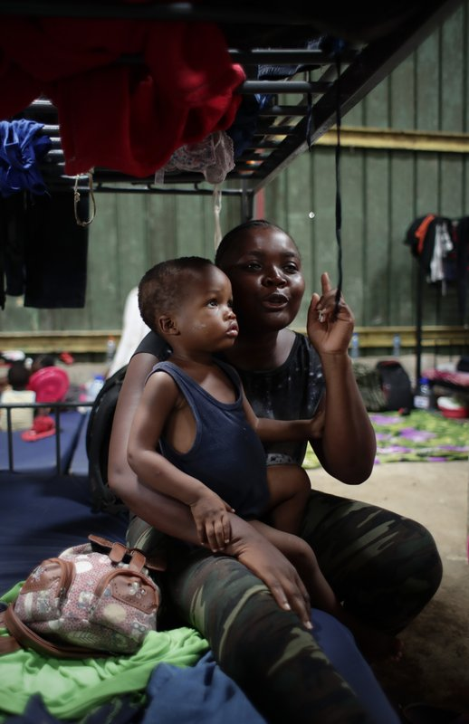 In this May 10, 2019 photo, Hatian migrant Venise Felizor holding her son Wesly Simeon Felizor, speaks during an interview at a shelter in Peñitas, Darien Province, Panama. (AP Photo/Arnulfo Franco)