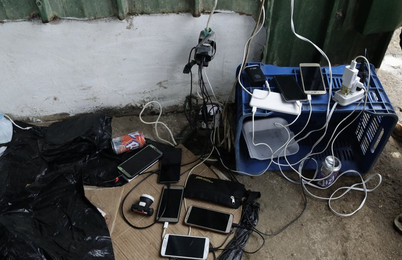 In this May 10, 2019 photo, migrant's cell phones charge their batteries at a shelter in Peñitas, Darien Province, Panama. (AP Photo/Arnulfo Franco)