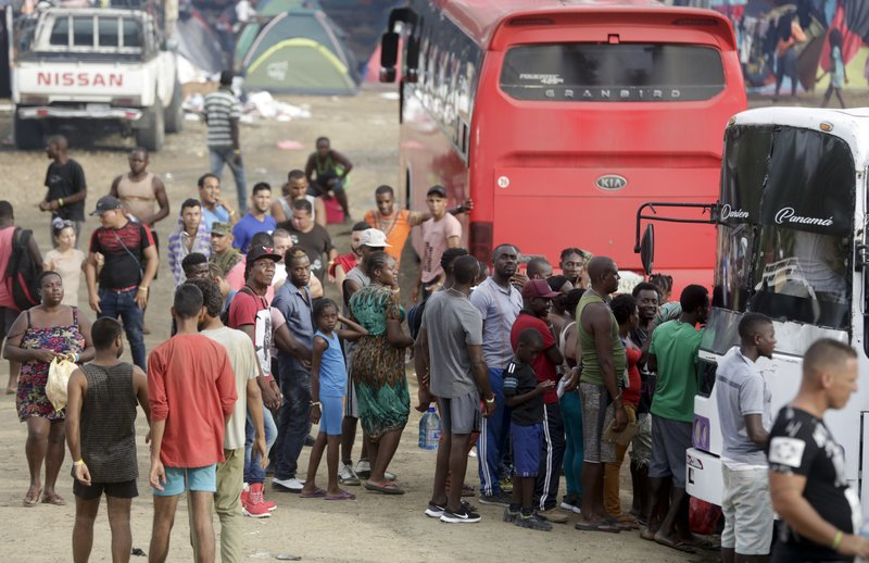In this May 10, 2019 photo, a group of migrants wait for space in a bus that will take them on their trip north, in Peñitas, Darien Province, Panama. (AP Photo/Arnulfo Franco)