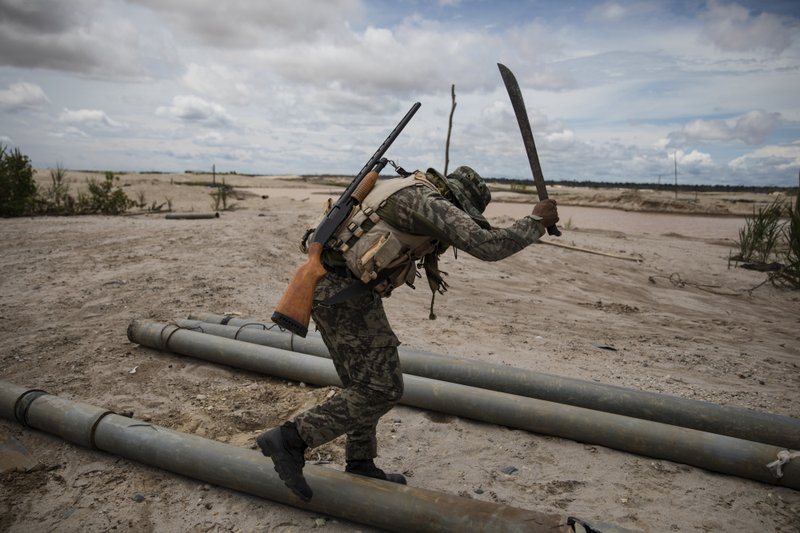 In this March 27, 2019 photo, a soldier hacks with a machete tubing used by illegal miners to mine gold, as part of