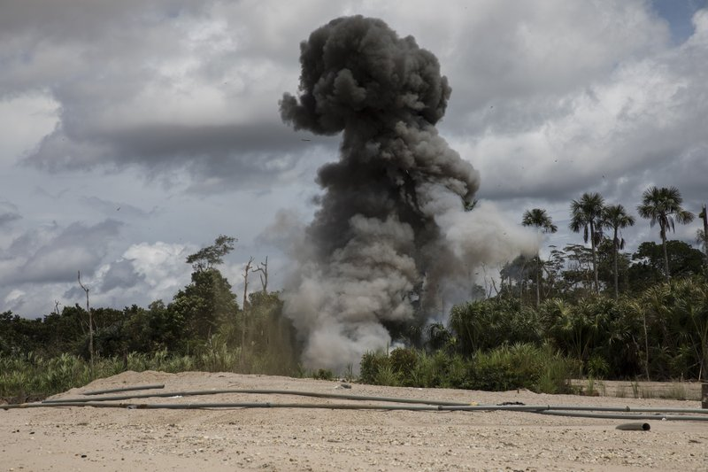 In this March 27, 2019 photo, a cloud of smoke rises after police dynamite machinery used by illegal miners as part of