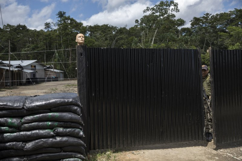 In this March 28, 2019 photo, a soldier peers out from inside a new police and military base in Peru's Tambopata province. (AP Photo/Rodrigo Abd)
