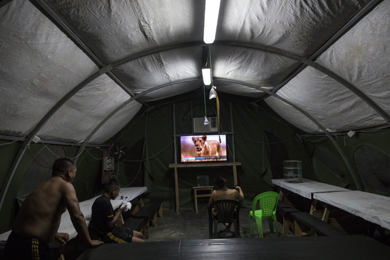 In this March 31, 2019 photo, soldiers watch a nature show in their tent at the Balata military and police base in Peru's Tambopata province. (AP Photo/Rodrigo Abd)