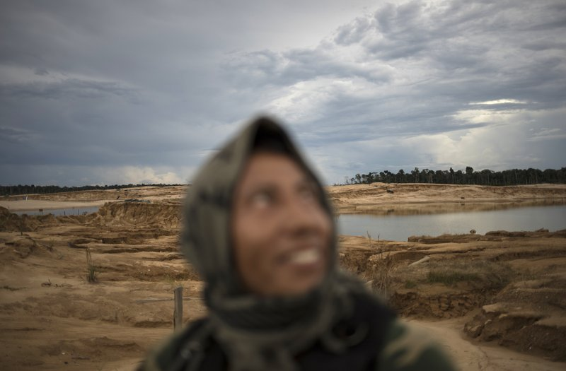 In this April 3, 2019 photo, a police officer smiles while riding in a pick-up truck during a patrol in Peru's Tambopata province. (AP Photo/Rodrigo Abd)