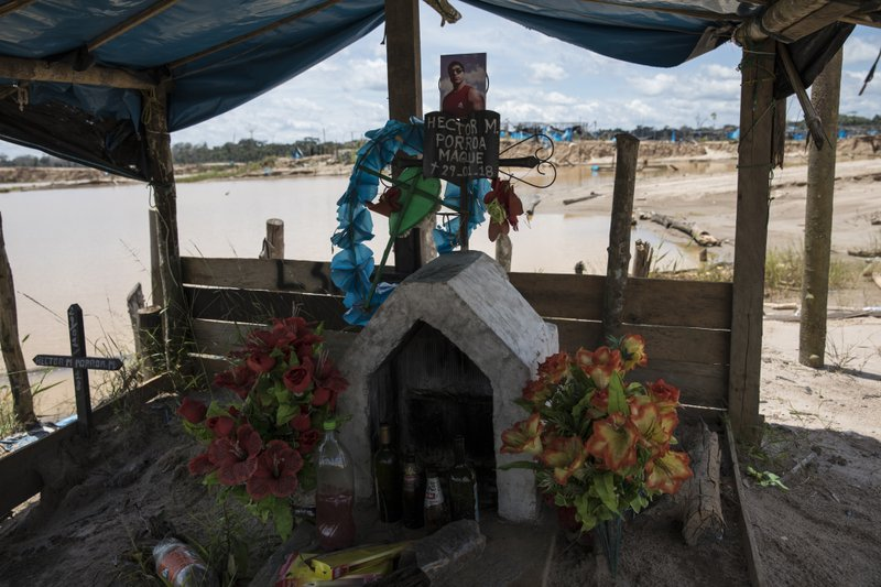 This March 28, 2019 photo shows a memorial adorned with artificial flowers and bottles of alcohol inside a former illegal gold mining camp that has been occupied by special forces and converted into the Balata police and military base, in Peru's Tambopata province. (AP Photo/Rodrigo Abd)