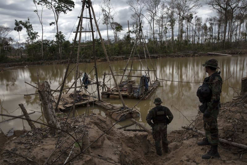 In this April 1, 2019 photo, police special forces stand next to illegal mining machinery in Peru's Tambopata province. (AP Photo/Rodrigo Abd)