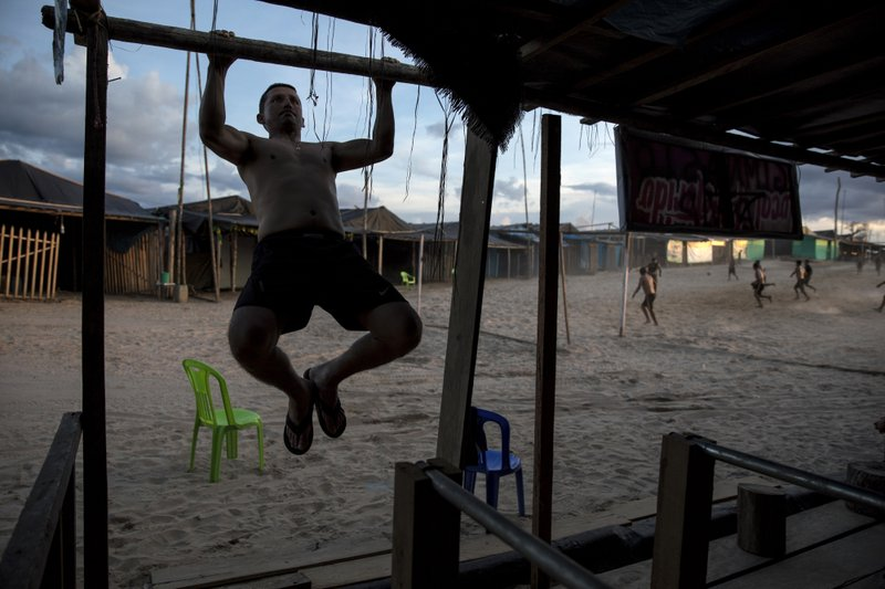 In this March 31, 2019 photo, Maj. Gustavo Cerdeña does pull-ups using the wood frame of a structure at the Balata police and military base, once an illegal gold mining camp in Peru's Tambopata province. (AP Photo/Rodrigo Abd)