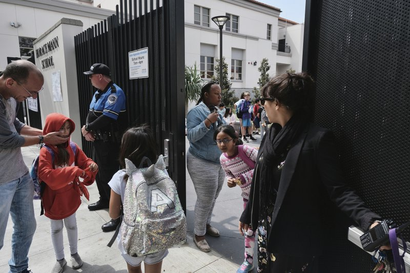 In this Monday May 13, 2019 photo Juliet Fine, right, the principal at Horace Mann School stands and watches as parents pick up their children after a school day in Beverly Hills, Calif. (AP Photo/Richard Vogel)