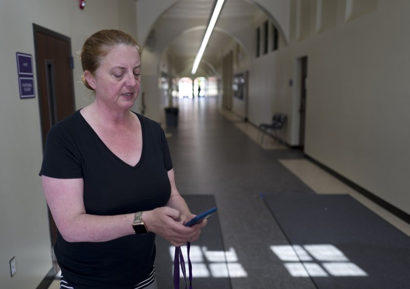In this Monday May 13, 2019 photo Lisa Bieler, a technology specialist for the Beverly Hills Unified School District checks her mobile photo in the hallway at Horace Mann School at her office in Beverly Hills, Calif. (AP Photo/Richard Vogel)