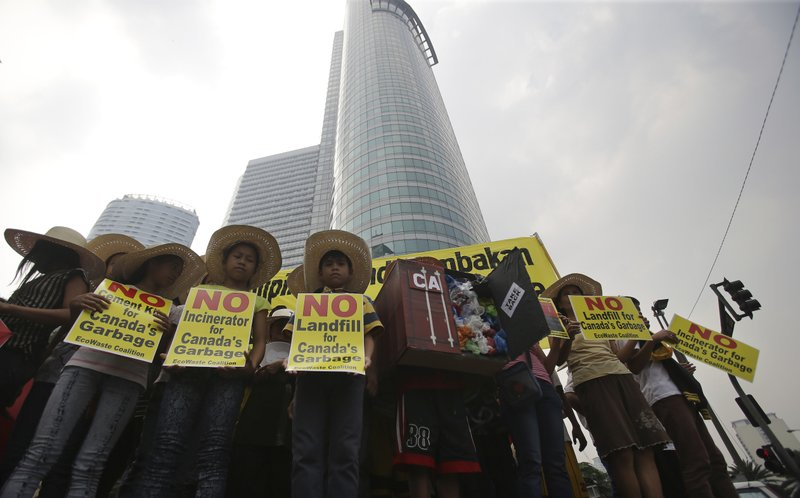 FILE - In this May 7, 2015, file photo, Filipino environmental activists hold slogans about the 50 containers of waste that were shipped from Canada to the Philippines two years ago, during a protest outside the Canadian embassy at the financial district of Makati, south of Manila, Philippines. (AP Photo/Aaron Favila, File)