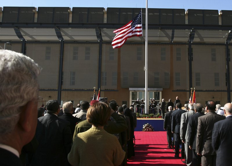 FILE - In this Jan. 5, 2009 file photo, people watch the U.S. flag as it is raised during a ceremony marking the opening of the new U. (AP Photo/Hadi Mizban, File)