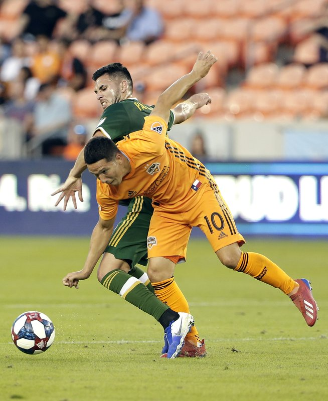 Portland Timbers midfielder Cristhian Paredes, left, and Houston Dynamo midfielder Tomas Martinez (10) battle for control of the ball during the first half of an MLS soccer match Wednesday, May 15, 2019, in Houston. (AP Photo/Michael Wyke)
