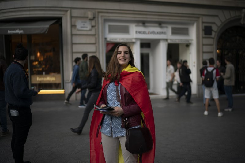 In this May 11, 2019 photo, far-right Vox supporter Amanda Puiggros, 22, distributes flyers after a party meeting in Barcelona, Spain. (AP Photo/Felipe Dana)
