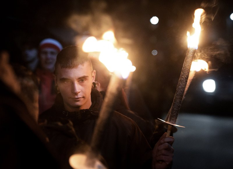 FILE - In this Wednesday, Nov. 9, 2016 file photo, demonstrators hold torches during a far-right Thuegida rally in Jena, Germany. (AP Photo/Jens Meyer)