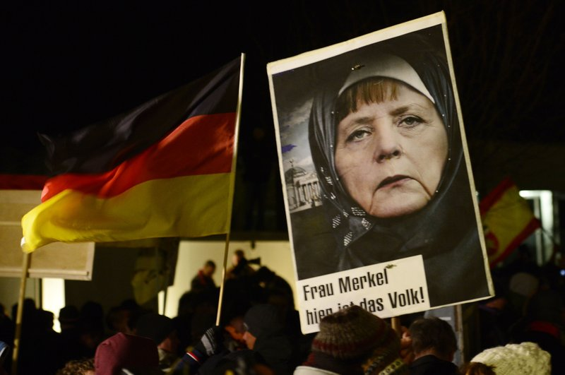 FILE - In this Jan. 12, 2015 file photo, a protestor holds a poster with a manipulated image of German Chancellor Angela Merkel wearing a headscarf and the Reichstag with a crescent on top, during a rally by the group Patriotic Europeans Against the Islamization of the West (PEGIDA) in Dresden, Germany. (AP Photo/Jens Meyer, File)