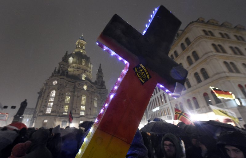 FILE - In this Monday, Feb. 29, 2016 file photo, an illuminated cross with a sticker reading