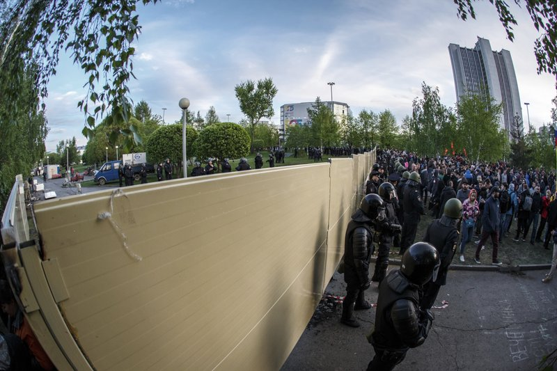 Demonstrators gather in front of a new builded fence blocked by police, to protest plans to construct a cathedral in a park in Yekaterinburg, Russia, Wednesday, May 15, 2019. (AP Photo/Anton Basanayev)